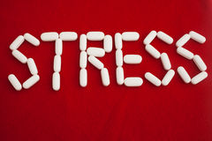 Stress. The word stress spelled out with white pills against a red background Stock Image