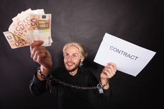 Man with chained hands holding contract and money. Stress at work, no freedom, pursuit of money concept. Mad man with chained hands holding money and contract Stock Image
