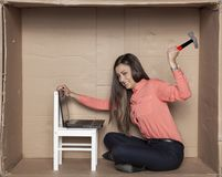 Stress at work, secretary holding a hammer in hand, blow on a la. Ptop, office situation Royalty Free Stock Photos