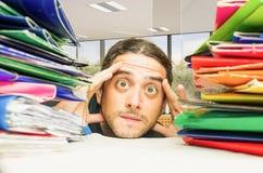 wage slavery modern slaves Stressed man headache at work office Stock Photos