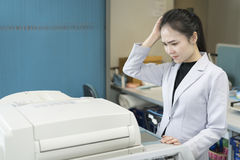 Stress young asian businesswoman looking at paper stuck in print stock images