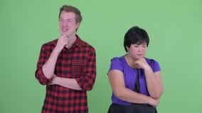 Stressad överviktig asiatisk kvinna med den lyckliga skandinaviska hipstermannen som tillsammans tänker stock video