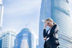 Stressad affärskvinna i staden arkivbild