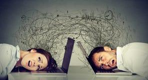 Stressad affärskvinna och man som vilar huvudet på bärbar datorsammanträde på tabellen som frustreras med de som utbyter med röra arkivfoton