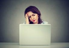Stressad affärskvinna som ser hennes bärbar dator royaltyfri foto