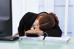 Stressad affärskvinnabenägenhet på skrivbordet Arkivbilder