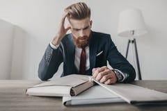 Stressad affärsman med dokument och mappar som i regeringsställning sitter på tabellen Arkivfoto