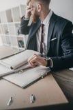 Stressad affärsman med dokument och mappar som i regeringsställning sitter på tabellen Arkivbild
