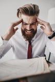 Stressad affärsman med dokument och mappar som i regeringsställning sitter på tabellen Arkivfoton