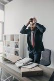 Stressad affärsman med dokument och mappar som i regeringsställning står på tabellen Royaltyfri Foto