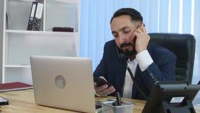Stressad affärsman som på en gång talar på många telefoner lager videofilmer
