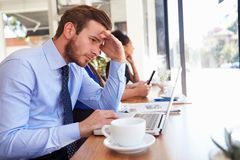 Stressad affärsmanUsing Laptop In coffee shop arkivfoto