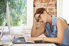 Stressad affärskvinna Working At Computer i modernt kontor Royaltyfria Bilder
