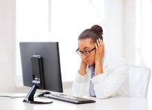 Stressad afrikansk kvinna med datoren arkivfoto