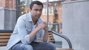 Stressad afrikansk man med att sitta för huvudvärk som är utomhus- stock video