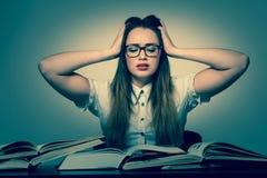 Stressad asiatisk caucasian kvinnastudent som lär i högar av böcker Fotografering för Bildbyråer
