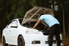 Stressad asiatisk man som ser motorn av den brutna bilen royaltyfri fotografi