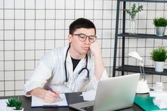 Stressad doktor i klinik under tryck Yrkesfel, behandlingfel och fel eller försummelse Arbetsplatspennalism royaltyfria foton