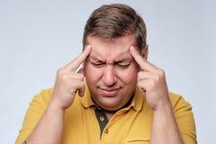 Stressad fet man i gul t-skjorta med fingrar på tempellidande från huvudvärk Arkivbild