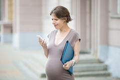 Stressad gravid affärskvinna som irriteras med hennes telefon arkivbild
