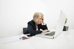 Stressad hög affärskvinna som i regeringsställning använder bärbara datorn på skrivbordet Royaltyfri Bild