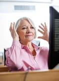 Stressad hög kvinna som ser datoren i klassrum Royaltyfri Bild