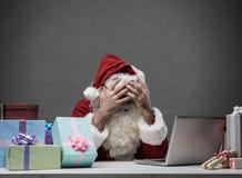 Stressad jultomten som förbinder med hans bärbar dator Royaltyfri Foto