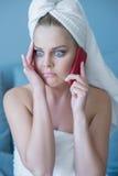 Stressad kvinna i badlakan med mobiltelefonen Royaltyfri Fotografi