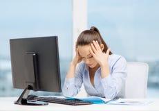 Stressad kvinna med datoren och dokument Arkivfoto