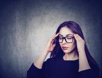 Stressad kvinna med exponeringsglas som lider från eyestrain som har huvudvärk Arkivfoton