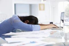 Stressad kvinna som arbetar på bärbara datorn i inrikesdepartementet arkivfoton