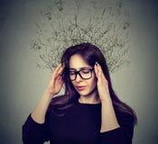 Stressad kvinna som har huvudvärk med bekymrat framsidauttryck och hjärnan som smälter in i många linjer frågefläckar royaltyfri foto