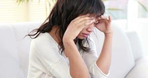 Stressad kvinna som rymmer hennes huvud på soffan lager videofilmer