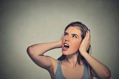 Stressad kvinna som täcker henne öron som ser upp arkivbilder