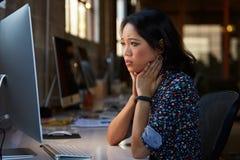 Stressad kvinnlig formgivare Works At Computer i modernt kontor arkivfoto