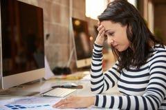 Stressad kvinnlig formgivare Works At Computer i modernt kontor royaltyfri foto