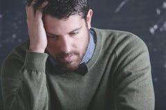 Stressad lärareman som framme bär stilfull kläder en svart tavla. Arkivbild