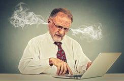 Stressad äldre gamal man som använder datoren som blåser ånga från öron Royaltyfri Bild