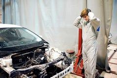 Stressad mekanikerman i det vita likformiginnehavhuvudet mot bilen i reparationsgarage arkivfoton