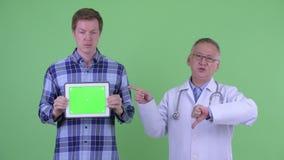 Stressad mogen japansk mandoktor med den unga mannen som visar den digitala minnestavlan och ner ger tummar lager videofilmer