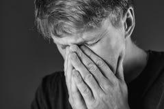 Stressad och ledsen man som täcker hans framsida med händer Sorgsenhet förtvivlan, tragedibegrepp monokrom royaltyfri bild