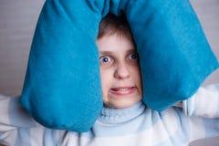 Stressad pojke som täcker hans huvud och öron som ut blockerar ljudet w royaltyfri bild