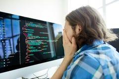 Stressad programmerare framme av datoren fotografering för bildbyråer