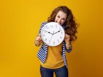 Stressad stilfull kvinna mot den stickande klockan för gul bakgrund Arkivbild