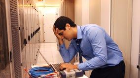 Stressad tekniker som använder bärbara datorn stock video