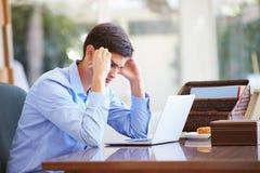Stressad tonårs- pojke som hemma använder bärbara datorn på skrivbordet Arkivbild