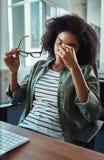 Stressad ung affärskvinna i kontoret arkivfoto