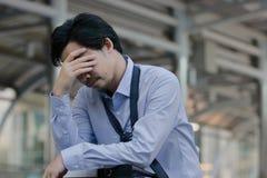 Stressad ung asiatisk känsla för affärsman som tröttas och evakueras med hans jobb arkivbild