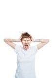 Stressad ung kvinna med huvudvärkinnehavhänder på head och att skrika med stängda ögon Arkivbild