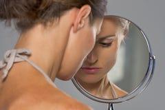 Stressad ung kvinna som ser i spegel royaltyfri bild